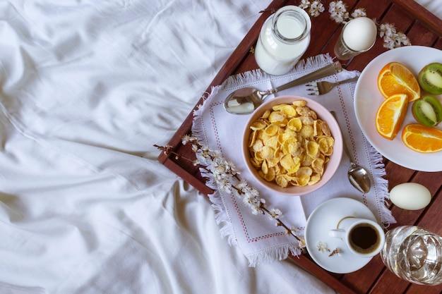 春の花が付いているベッドでロマンチックな朝食。フラットレイアウト、コピースペース