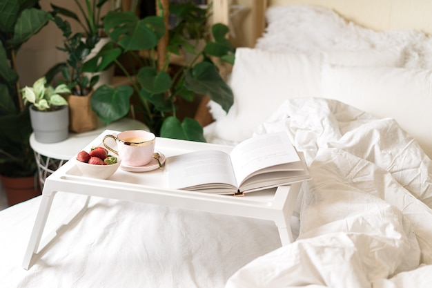 Романтический завтрак в постели с кофе и клубникой.