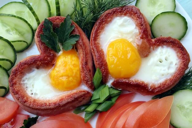 ロマンチックな朝食、ハートの形のソーセージとスクランブルエッグ。