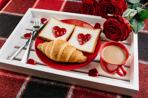 Romantic breakfast on tray on table