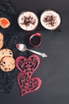 Romantic breakfast. two cups of coffee, cappuccino with chocolate cookies and biscuits  near red hearts on black table background. valentine day. love. top view.