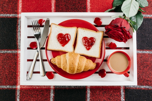 Romantic breakfast on white tray on table