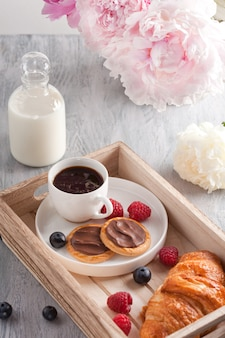 Romantic breakfast with coffee, croissant, chocolate cookies and berries