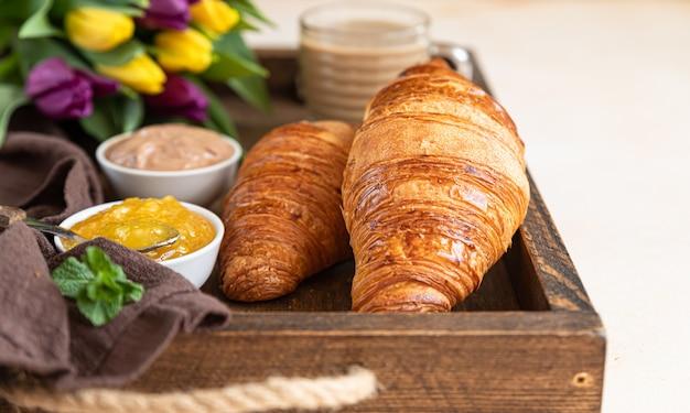 Romantic breakfast with crispy croissants, jam chocolate cream, coffee and colorful tulips