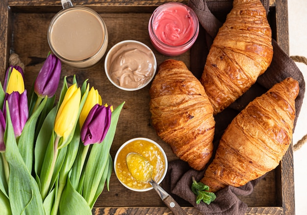 Romantic breakfast with croissants, jam, chocolate cream, coffee and tulips on wooden tray