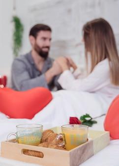 Colazione romantica sul vassoio di legno sul letto