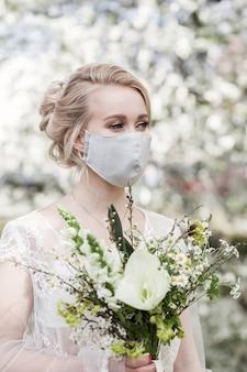 웨딩 드레스와 의료 보호 마스크와 꽃의 꽃다발에 로맨틱 한 신부