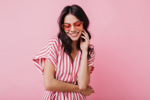 Романтичная шатенка в модных очках-сердечках позирует с застенчивой улыбкой. фотография в помещении изящной молодой женщины в летнем наряде и аксессуарах.