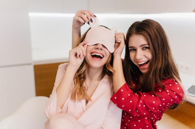 Romantica ragazza dai capelli castani indossa un pigiama rosso con un sorriso. foto di giocose sorelle in abiti da notte che si divertono.