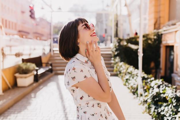 週末に路上で笑っているロマンチックな茶色の髪の女性。ポジティブな感情を表現する短いヘアカットで洗練された女性モデルの屋外ショット。