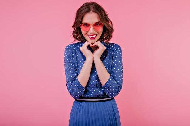 笑顔でポーズをとるエレガントな青い服装のロマンチックなブルネットの女性。ピンクの壁で笑っているサングラスの美しい女性モデルの屋内ショット。