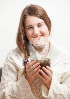 Romantic brunette woman holding cup of tea. vapor forming heart
