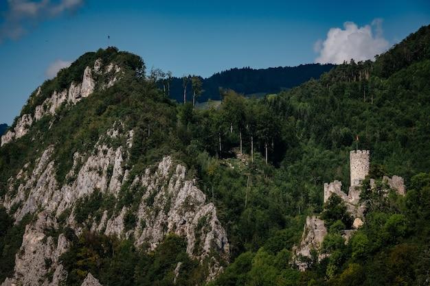 スイスアルプスの山間の谷の丘の上にあるロマンチックな城。背景には青い空があり、岩の下に小さな村があります。