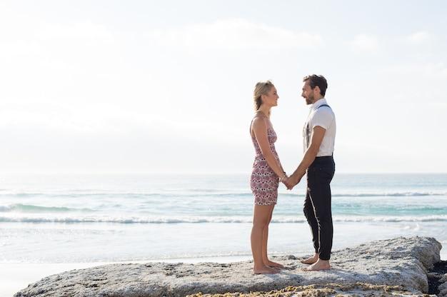 手をつないでビーチに立っているロマンチックなカジュアルな若いカップル