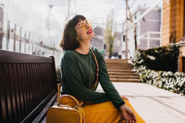 Романтичная кавказская девушка в модном зеленом свитере позирует на улице. открытый выстрел блаженной модели брюнетки женской охлаждая на скамейке.