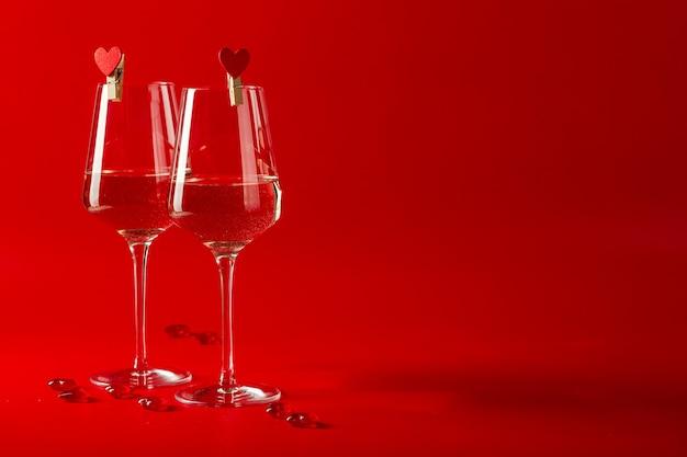Романтическое празднование дня святого валентина. два полных бокала вина и декоративные стеклянные сердечки
