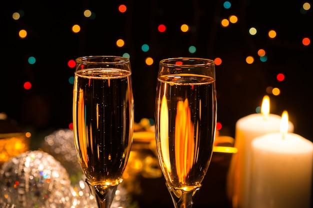 燃えるろうそくとカラフルなパーティーライトの背景ボケでクリスマスと新年を祝うために2つのエレガントなフルートでロマンチックなシャンパン