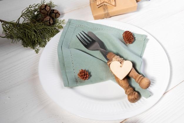 Романтическая рождественская сервировка стола с экологически чистой льняной салфеткой и деревянным сердечком