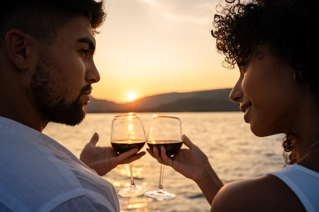 Romantic close-up of a mixed race couple toast with glasses of red wine crossed by the light of the setting sun on a lake