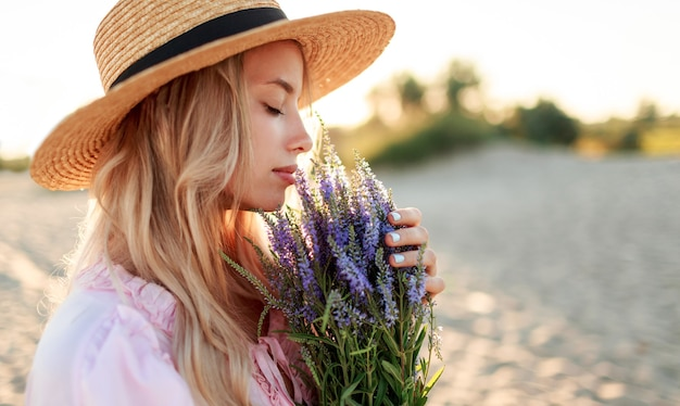 Romantic close up portrait  o charming blonde girl in straw hat  smells    flowers   on   the evening beach,  warm sunset colors. bouquet of lavender. details.