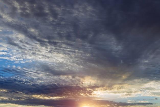 Романтический красочный закат на закате, синие и оранжевые облака текут в небе, величественный летний пейзаж