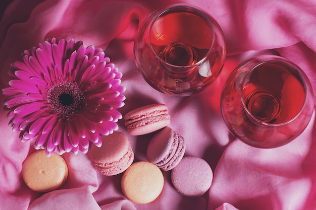 Romantic composition of flowers, sweets and wine on a pink background