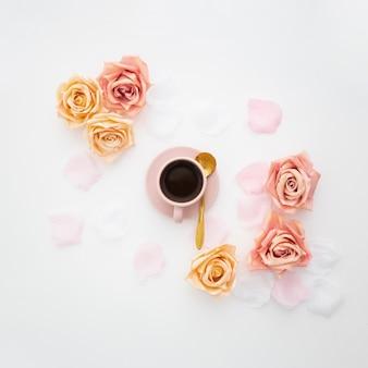 Romantic composition made with a pink cup of coffee and roses