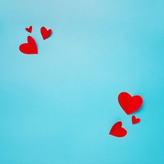 Romantic composition made with red hearts on blue background with copyspace for text