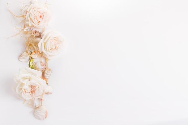 흰색 바탕에 이국적인 조개, 굴, 불가사리, 흰 장미의 낭만적인 구성. 열 대 여름 휴가 또는 생일, 결혼식 날 개념. 평평한 평지, 평면도. 해양 디자인.