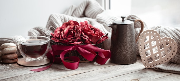 Romantic composition for valentine's day with a cup of tea, a teapot and decorative elements.