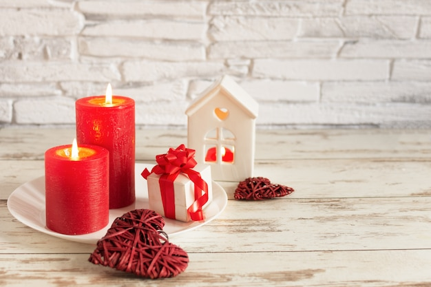 Romantic composition for valentines day with candles and hearts on wooden table over white brick wall.
