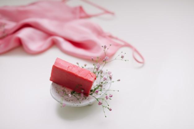 セラミック皿と銀のドレスとピンクの石鹸でロマンチックな構成
