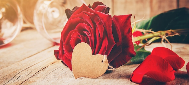 Romantic composition with red rose and wine glasses