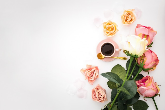 Romantic composition with roses, petals and pink cup of coffee with copy space