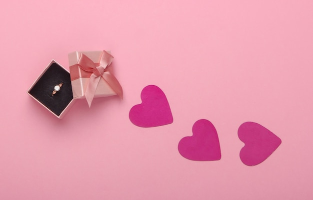 Romantic concept. box and golden ring with a diamond, hearts on the pink pastel.