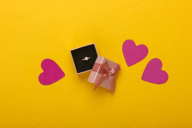 ロマンチックなコンセプト。ボックスにダイヤモンドが入った金の指輪、黄色のハート。