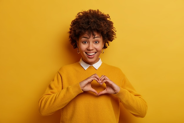 Romantic concept. pretty glad girl does heart symbol with hands, wears casual jumper, confesses in love to boyfriend, wears yellow neat jumper, smiles happily. volunteer has social responsibility