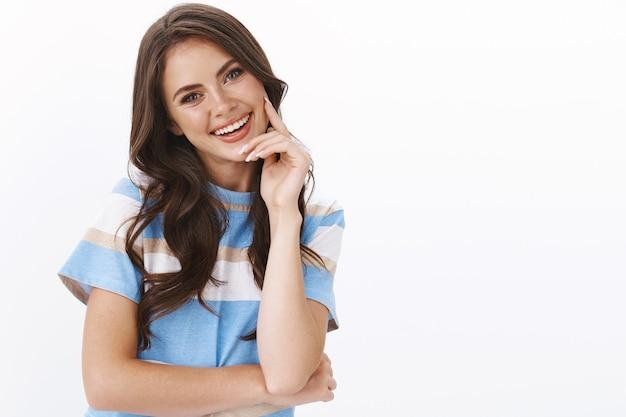 Romantica donna attraente e civettuola che fa sguardi civettuoli, tocca la guancia tenera e sorride dolcemente, inclina la testa seducente, ridacchia sorridendo felice a trentadue denti, goditi una piacevole conversazione piacevole, muro bianco
