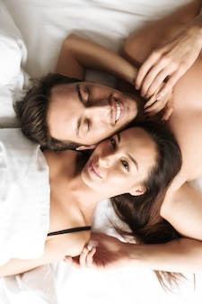 Romantic couple 30s hugging together, while lying in bed at home or hotel apartment