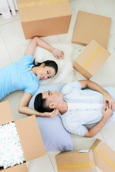 Romantic couple among boxes on floor