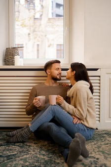 집에서 로맨틱 커플. 매력적인 젊은 여자와 잘 생긴 남자는 시간을 보내고 즐기고 있습니다