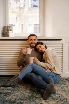 自宅でロマンチックなカップル。魅力的な若い女性とハンサムな男性が時間を過ごすことを楽しんでいます