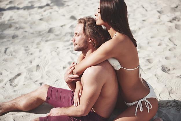 Una coppia romantica sulla spiaggia in costume da bagno, bei giovani sexy.