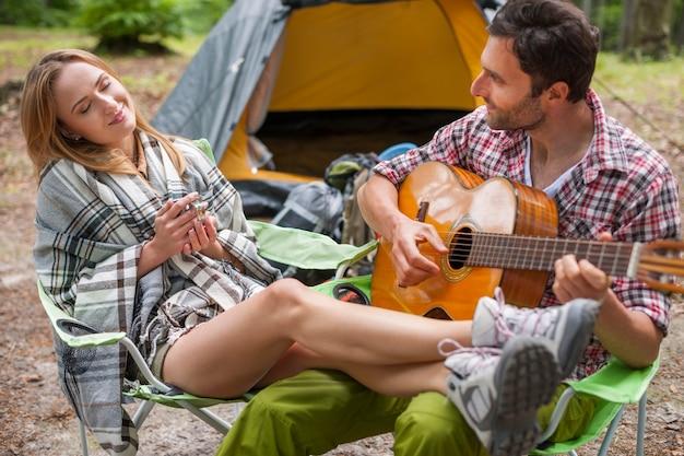 Coppia romantica in un campeggio. uomo che suona la chitarra.