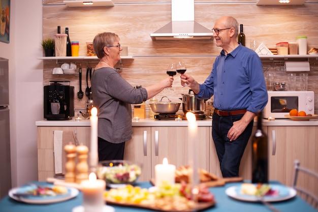 彼らの関係の記念日を祝うロマンチックなカップルのチャリンという音のメガネ。健康的な食事の間に楽しい会話をして話すのが大好きな老夫婦。