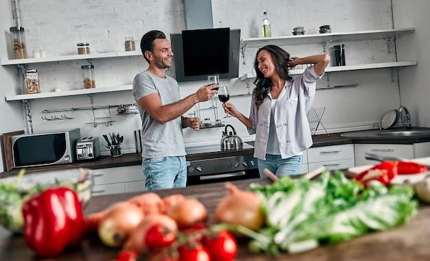 Романтическая пара танцует на кухне с бокалами вина. красивый мужчина и привлекательная молодая женщина веселятся вместе, делая салат. концепция здорового образа жизни.