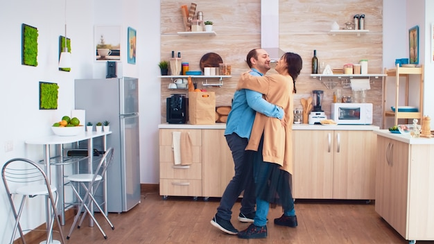 Romantic couple dancing in kitchen while food is getting reading on gas cooker. cheerful happy young family together dance. fun love affection romance leisure romantic music for enjoynment