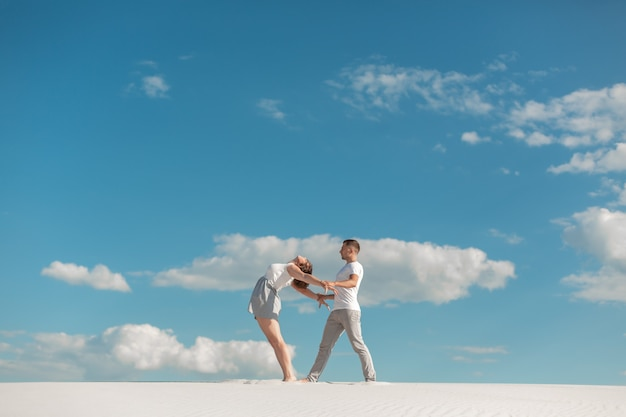 Romantic couple dancing in sand desert at blue sky background.