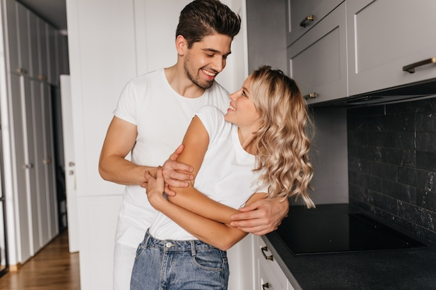 Romantic couple dancing together with sincere smile. indoor portrait of happy family posing in kitchen.