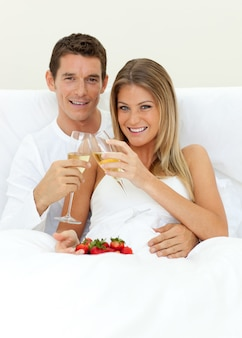Romantic couple drinking champagne with strawberries